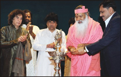 City Police Commissioner Dr. M.A. Saleem and Sri Ganapathy Sachchidananda Swamiji are seen lighting the lamp to inaugurate the music concert as Tabla Maestro Zakir Hussain and other artistes look on.