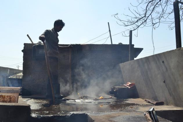A staff member treats the printed and dyed fabric with boiling water at the ajrakh workshop of Jabbar Khatri in Dasada, near Bhuj