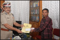City Police Commissioner Dr. M.A. Saleem is seen presenting the cash prize and citation to auto driver Pradeep.