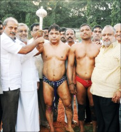 MLA G.T. Devegowda is seen presenting a silver mace to city's Pahilwan Ahmed on winning traditional wrestling bout against Pahilwan Yallappa of Dharwad. Also seen are MLA S.R. Mahesh and others.