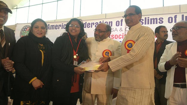 [Saima Rasheed, who accomplished unique achievement of having garnered 100 per cent marks in Std. XII in Punjab Higher Secondary Board examination 2015, being presented gold medal, Certificate of Excellence and a special cheque of Rs. 10,000/- by Madhya Pradesh Chief Minister Shivraj Singh Chouhan at the AFMI Internation Convention in Bhopal.]