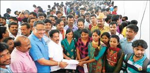 Minister Tanveer Sait and MLA M.K. Somashekar are seen handing over offer letter to a selected candidate at the Job Mela in city yesterday as others look on.