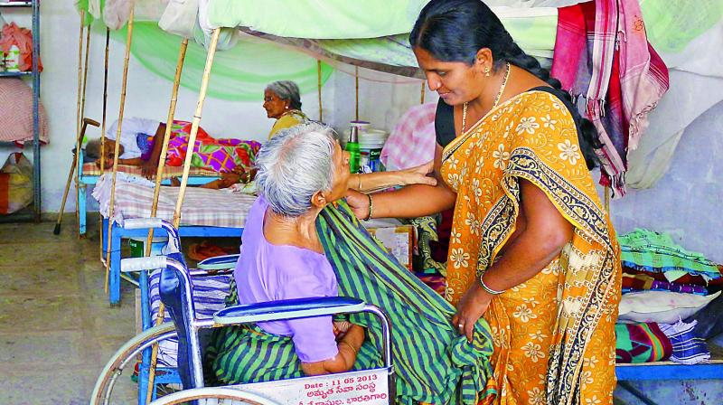 Yakub Bee helps dress a handicapped elderly lady, resident at the Sahrudaya old age home on Monday. (Photo: DC)