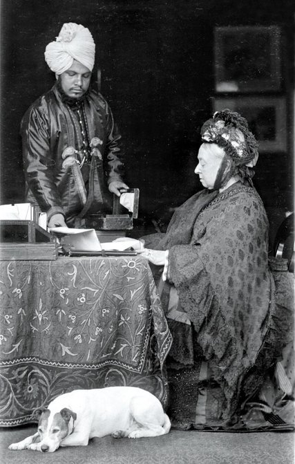 Queen Victoria at her desk, assisted by her servant Abdul Karim, the munshi.