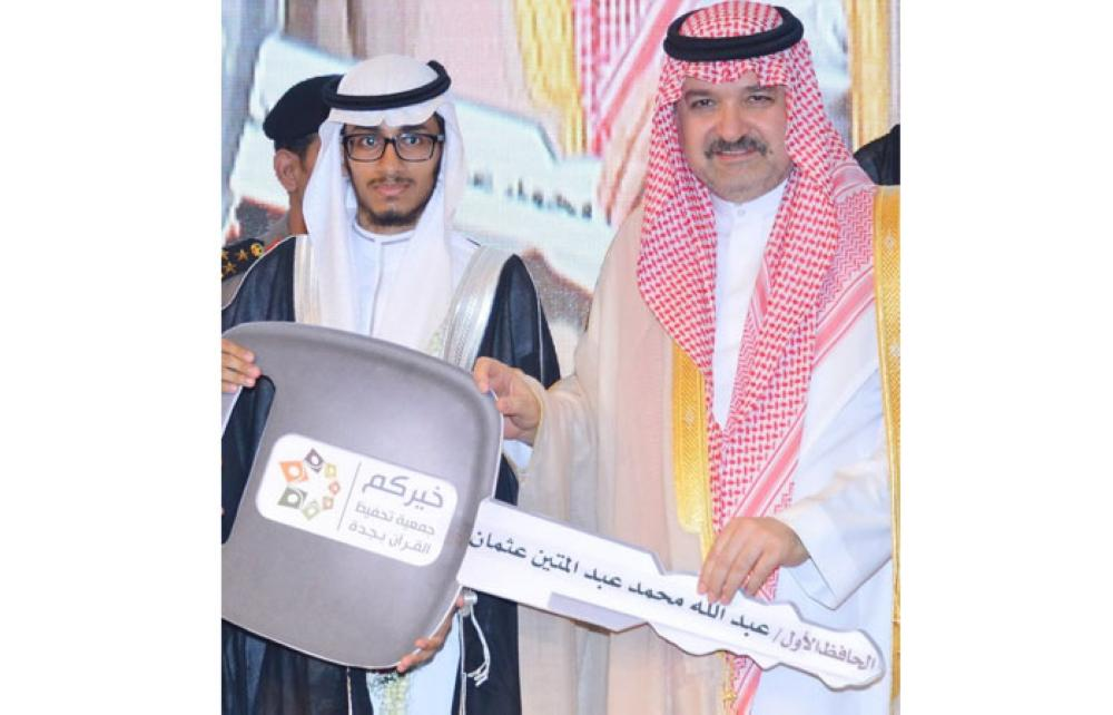 Prince Mishaal Bin Majed, governor of Jeddah, presents Abdullah Abdul Mateen Usmani the key of the car he won as first prize in the Quran memorization project